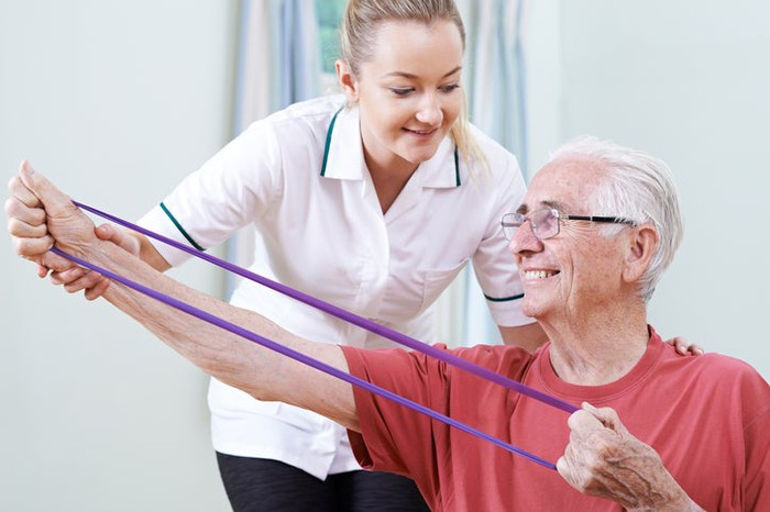 A physical therapist assists a senior man with an exercise.