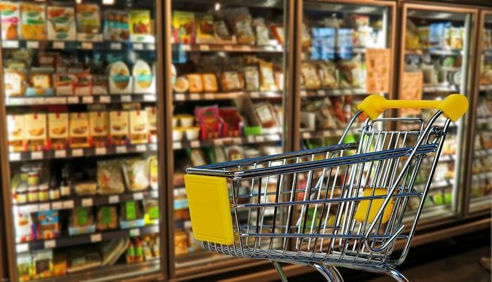 A grocery cart next to a supermarket freezer.