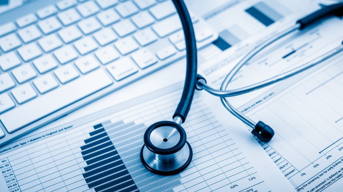 A stethoscope sits on top of financial statements, which are spread out next to a computer keyboard.