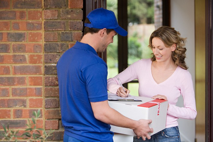 A customer signs for a package delivery at her home.