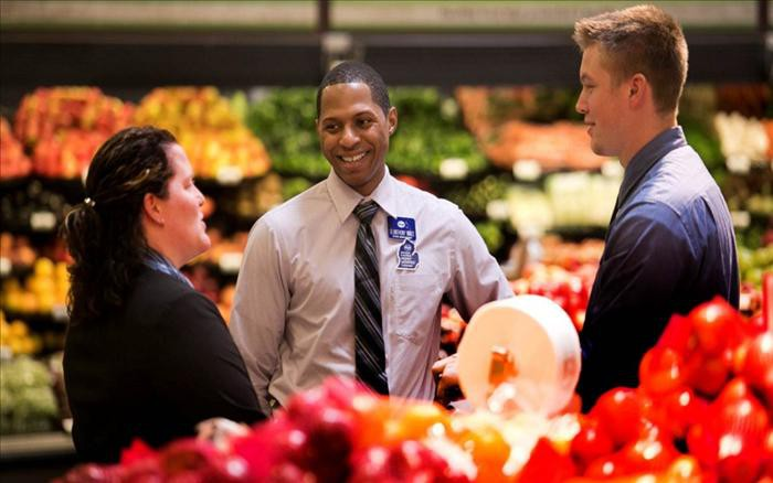 A Kroger employee talks with two people in the produce section.
