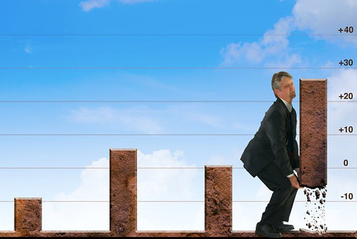 Picture of a man super-imposed on the image of a chart. The man is lifting the final bar.