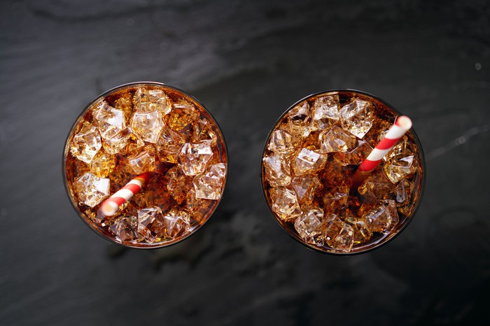 Two glasses viewed from above, filled with soda and ice