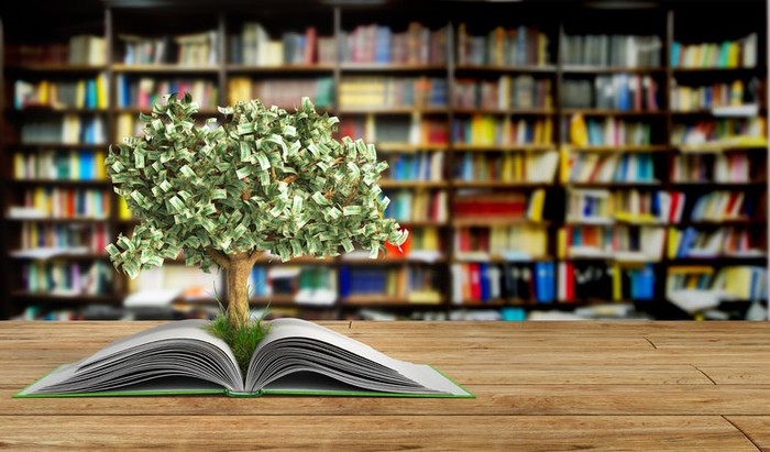 Tree with stylized dollar-bill leaves growing out of an open book, on a table in a library