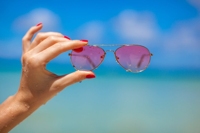 Woman's hand holding up rose-colored glasses