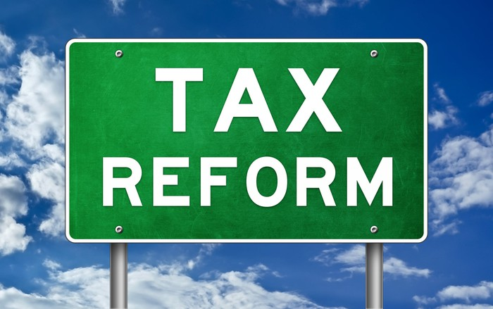 "A green road sign with the words ""tax reform"" on it, sitting against a blue sky."