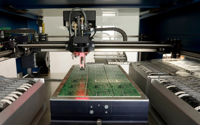 Machines are producing a batch of printed circuit boards.