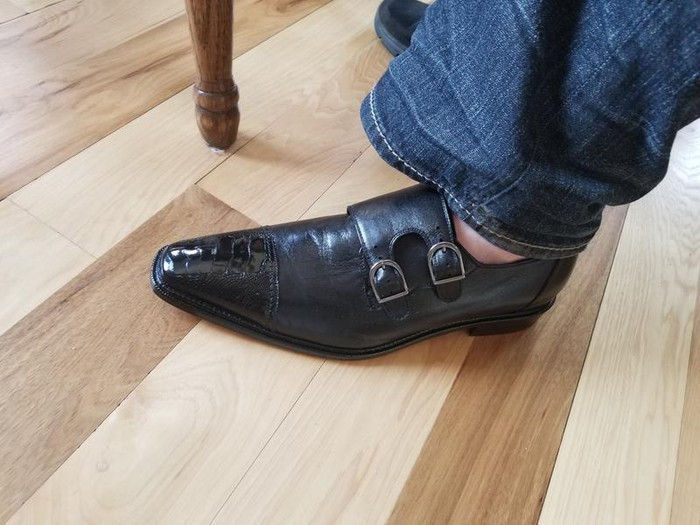 Pictured from about the knee down is a denim-clad leg and a sockless foot in a man's shoe