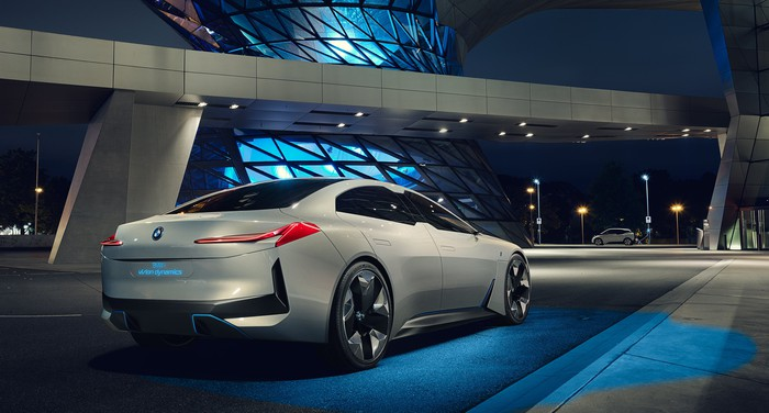 The i Vision Dynamics, a sleek sedan, is shown from a rear three-quarter view, parked at a curb at BMW's headquarters at night.