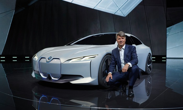 BMW CEO Harald Krueger is squatting next to the i Vision Dynamics, a sleek-looking white sedan.