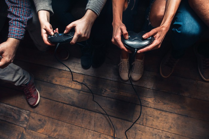 Overhead view of men's hands holding video game controllers while playing a game.