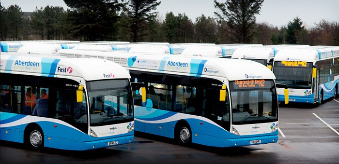 Hydrogen powered buses sitting in a parking lot.
