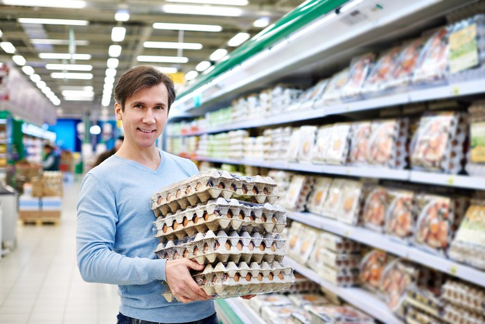 A man stands in a grocery aisle holding trays of eggs piled on top of one another