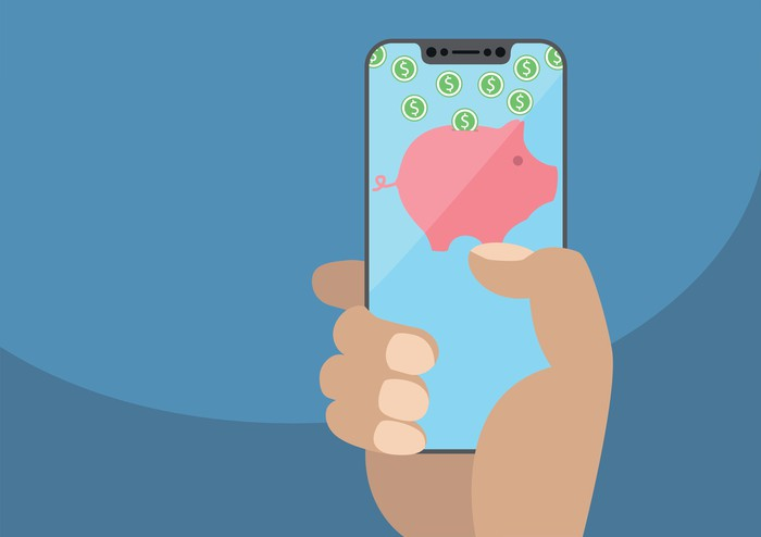 A hand holding a smartphone displaying a piggy bank with cash.