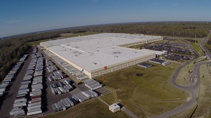 Ariel view of a large industrial building with a flat roof and lots of trailers in the lot and in the doors of the distribution center.