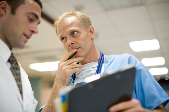 Two doctors reading a patients' clipboard and having a discussion.