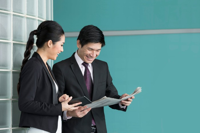 A businessman and businesswoman read the newspaper.