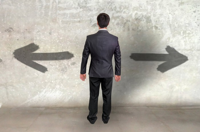 Businessman standing in front of arrows on wall pointing left and right