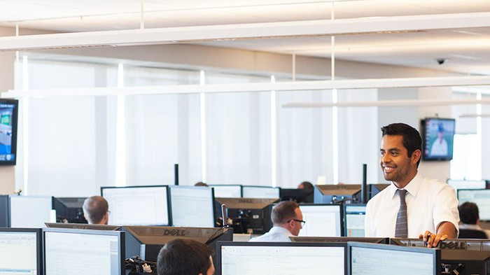Goldman Sachs employee standing up in a room of double-monitor workstations.