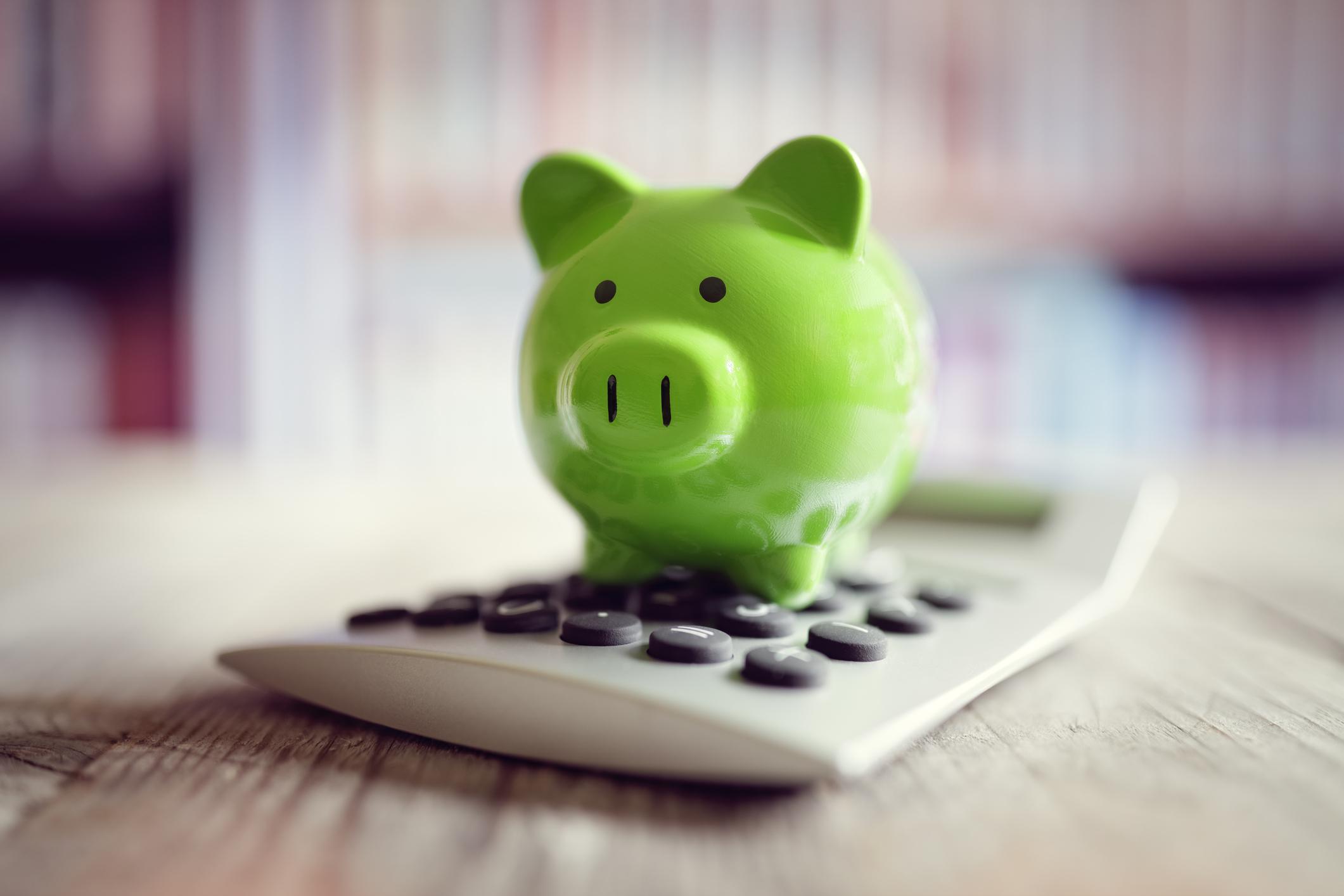 A green piggy bank sits atop a calculator on a wooden surface.