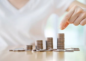 Woman stacking coins in rising piles