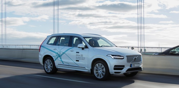 A white Volvo SUV with self-driving sensors is shown in traffic on a bridge.