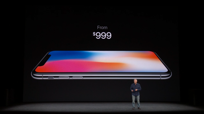 """Phil Schiller standing in front of a display featuring an iPhone X with the words """"From $999"""" above it."""