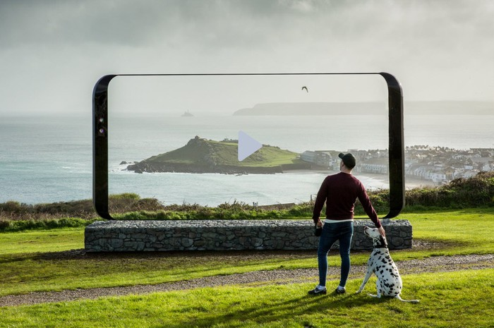A man and a dalmatian standing in front of an oversized Galaxy S8 featuring an image that blends perfectly with the surrounding landscape.