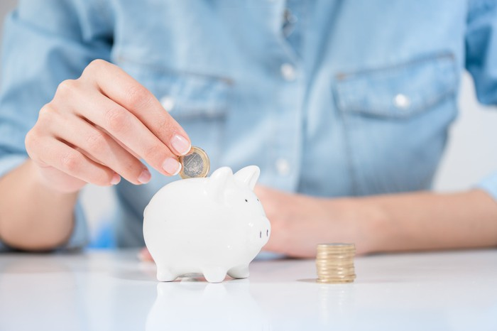 Woman in a blue shirt is putting coins inside a white piggy bank.
