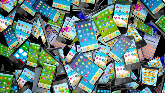 A large pile of smartphones, all turned on to showcase their colorful displays.