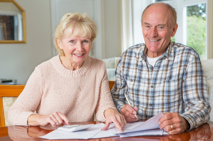 An older couple sitting at a table, reading paperwork.