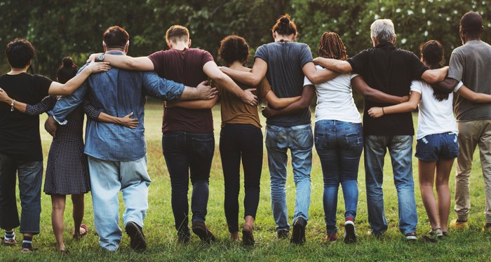 A group of friends walking with arms around each other