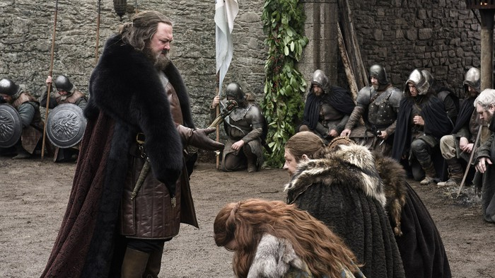 A character in Game of Thrones extends his hand to a group of kneeling people