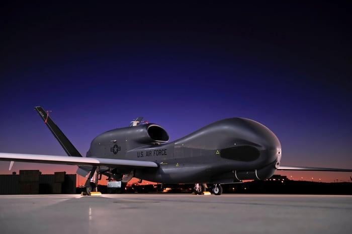 Global Hawk aircraft on the tarmac at an airport at night.