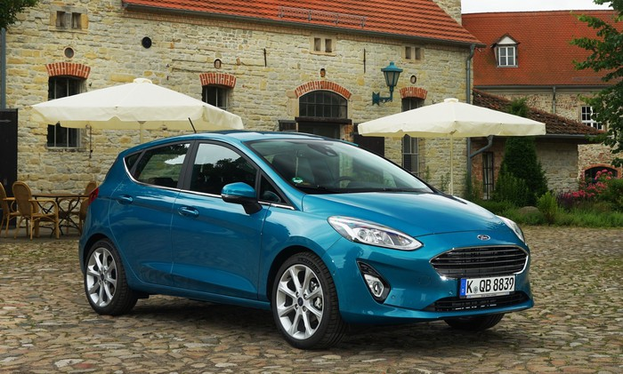 A 2018 Ford Fiesta hatchback in teal, with a European license plate, parked on a cobblestone surface in front of an old cafe.
