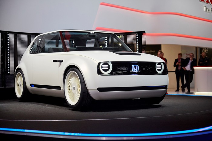 The Honda Urban EV Concept, a white hatchback with styling reminiscent of 1970s Honda Civics, on an auto-show stand.