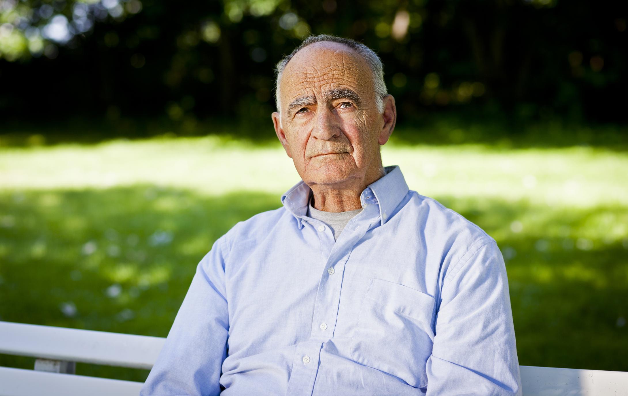 Somber senior man sitting on a bench