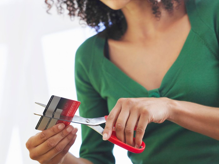 young woman cutting credit card in half with scissors