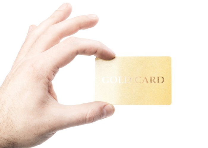 a hand holding a golden credit card