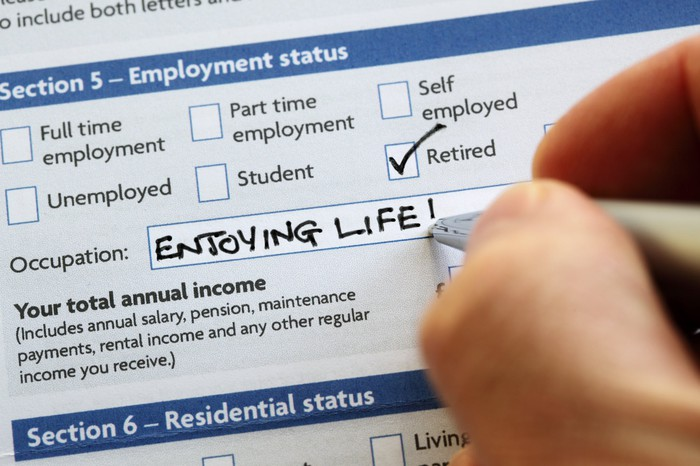 "A person writing ""enjoying life"" and checking the retired box for employment status paperwork."