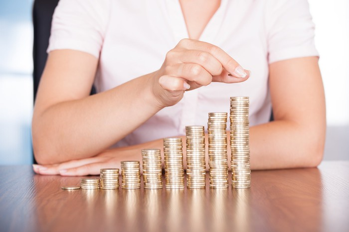 Woman stacking coins in rising piles.