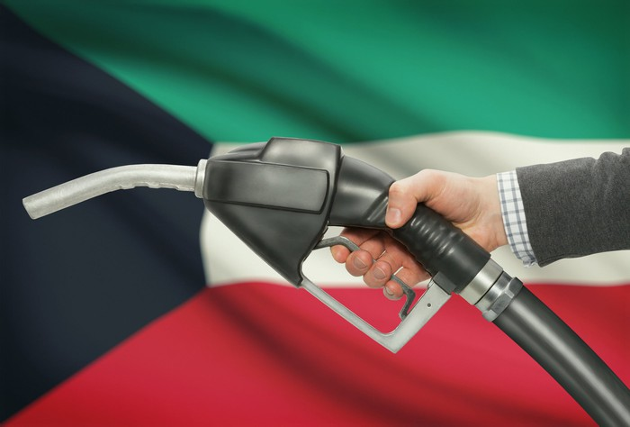 A hand holding a fuel pump with the Kuwaiti flag in the background.