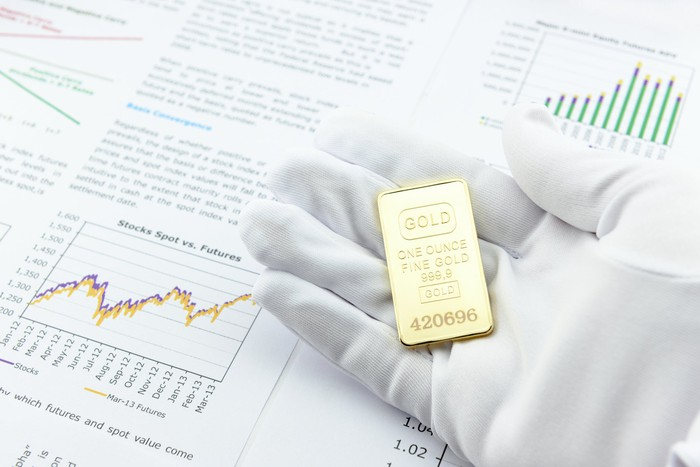 A hand with a white glove holding a gold ingot over a prospectus on investing in gold.