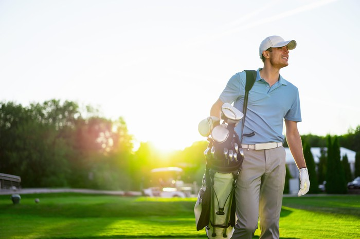 Man carrying golf clubs