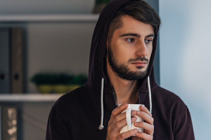 Serious younger man wearing a hoodie and clutching a coffee mug.