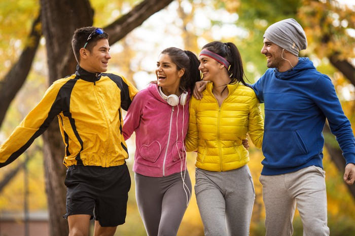 Group of friends walking together and wearing athletic apparel.
