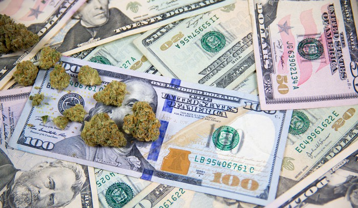Marijuana buds are scattered across a pile of U.S. currency of varying denominations.