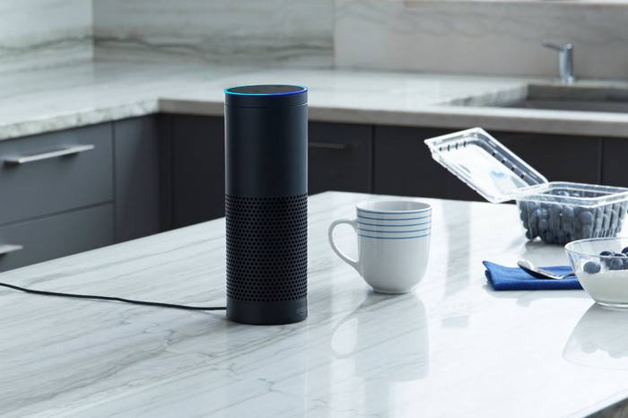 An Amazon Echo sits on a counter next to a coffee cup.