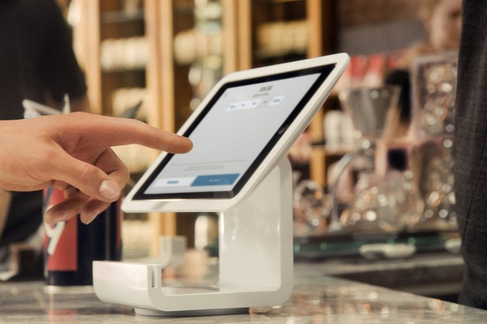 A hand on a Square Stand POS system.