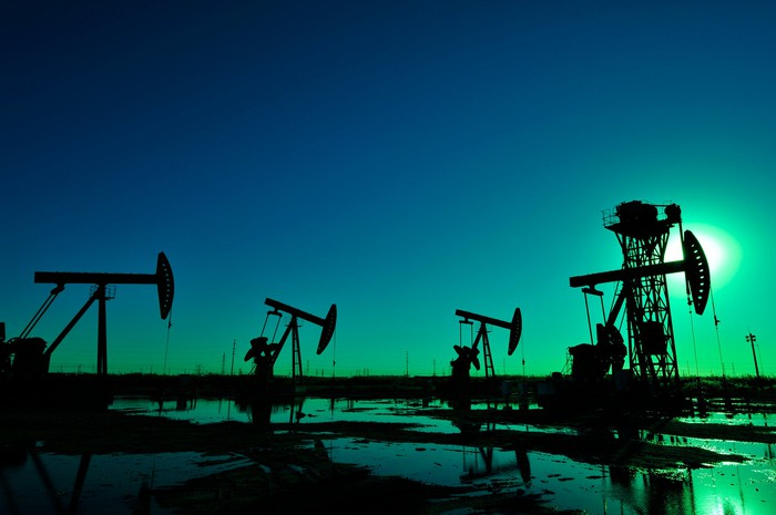 Oil wells in silhouette at night in a wet landscape.